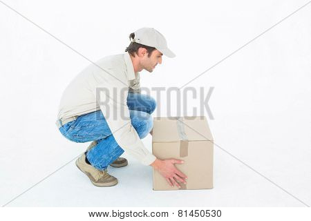 Side view of delivery man crouching while picking cardboard box against white background