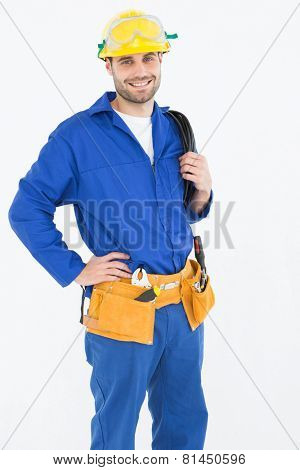 Portrait of happy construction worker standing with hand on hip against white background