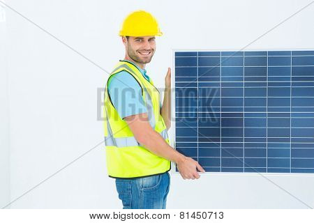 Side view portrait of happy architect holding solar panel against white background
