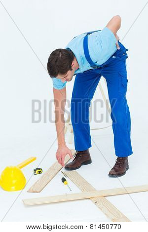 Full length of repairman picking up screwdriver while suffering from backache over white background