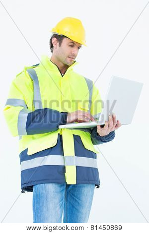 Portrait of male architect in reflective clothing using laptop computer over white background