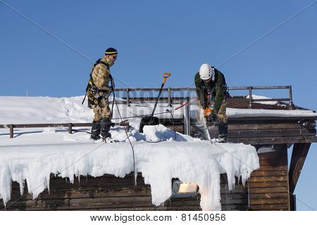 SOCHI, RUSSIA - JANUARY 22, 2015: Industrial climbers take off the snow and icicles from the roof