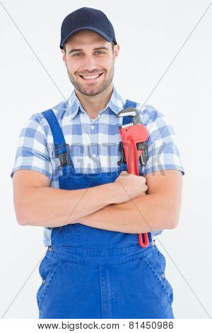 Portrait of confident young male repairman holding adjustable spanner on white background