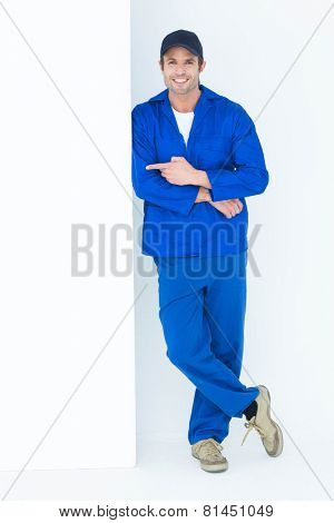 Full length portrait of confident mechanic pointing at bill board over white background