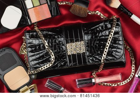 Beautiful Bag From Patent Leather And Cosmetics Lying On Red Satin