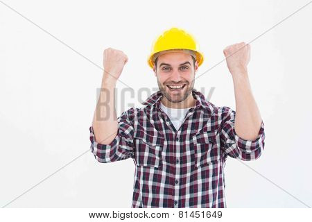 Portrait of successful male handyman clenching fists on white background