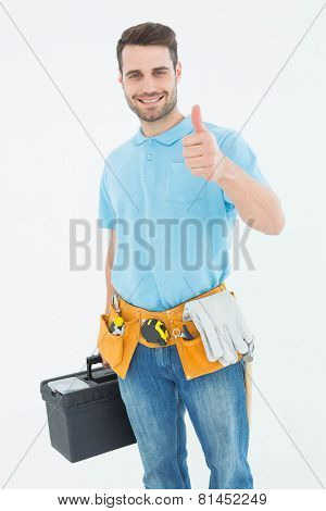 Portrait of happy carpenter gesturing thumbs up while carrying toolbox against white background