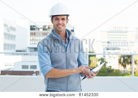 Portrait of happy male architect using digital tablet outdoors