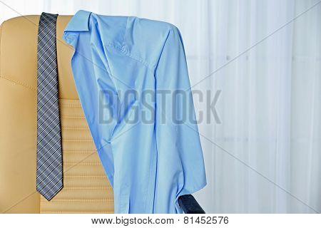 Men's clothes on chair with curtain on background
