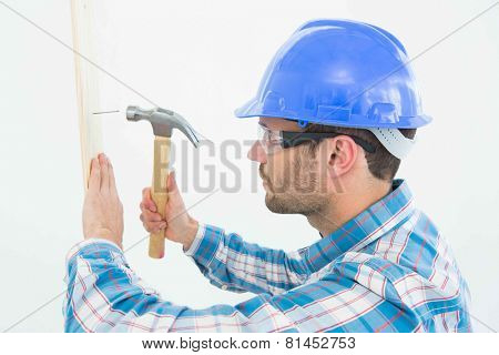 Side view of male carpenter hammering nail on wooden plank against white background