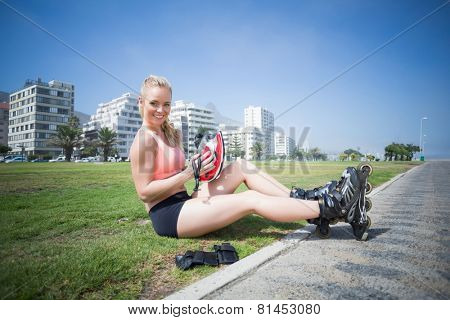 Fit blonde putting on her roller blades on a sunny day