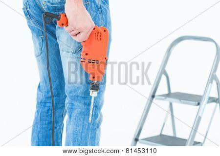 Cropped image of worker holding drill in front of step ladder over white background