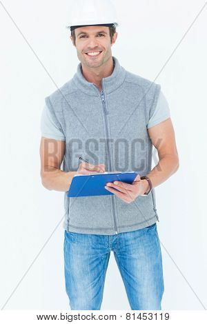Portrait of happy male architect writing notes on clip board against white background
