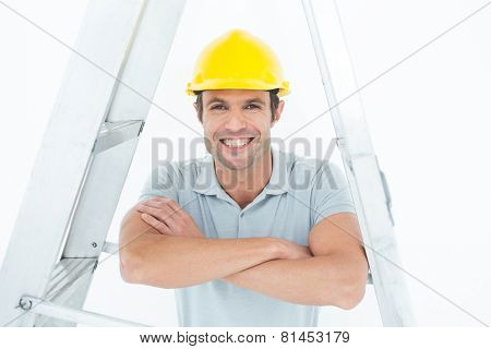 Portrait of happy carpenter leaning on step ladder over white background