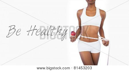 Woman holding apple and measuring her waist on white background