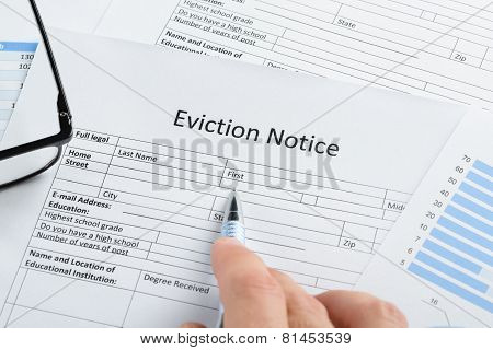Hand With Pen And Eyeglasses Over Eviction Notice