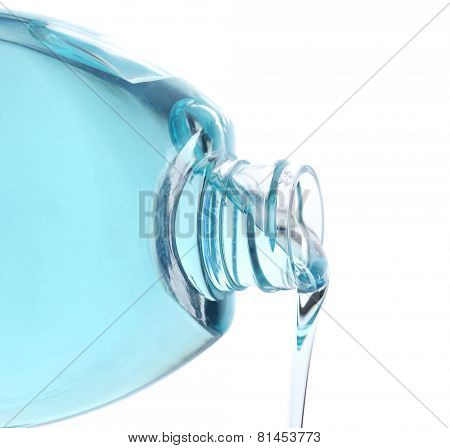 Cosmetic liquid pouring from bottle isolated on white