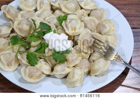 Pelmeni With Sour Cream, Butter, A Branch Of Parsley And Ground Pepper