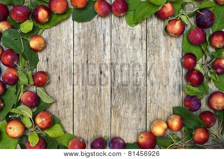 Beautiful frame of small red-ripe apples with green leaves on raw wooden background.