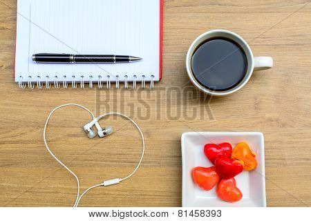 Office Table With Notebook, Headphone And Coffee Cup.