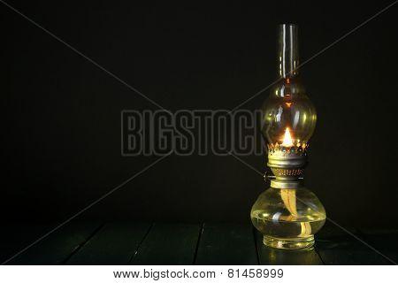 Kerosene lamp on wooden table and dark background