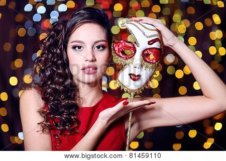 Beautiful girl with masquerade mask on bright background