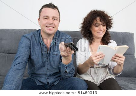Couple Reading Book At Home