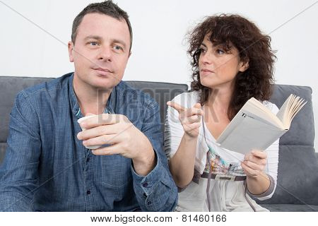 Couple In Living Room Reading A Book And Smiling