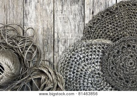 Grunge style decoration with old handmade crochet doilies, jute cord and rope over wooden background