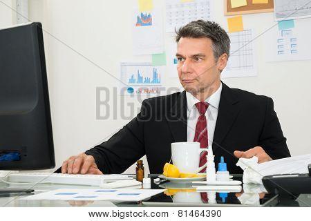 Sick Businessman Using Computer
