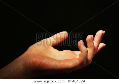 Female hand on dark background