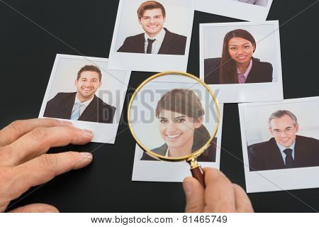 Businessman Looking At  Photograph Through Magnifying Glass