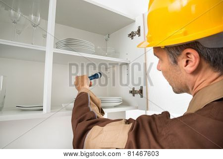 Pest Control Worker Checking Shelf