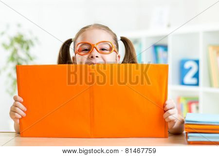 clever kid little girl behind of open book indoor