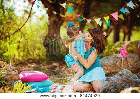 A young mother and little daughter relaxing in the Park on the grass.