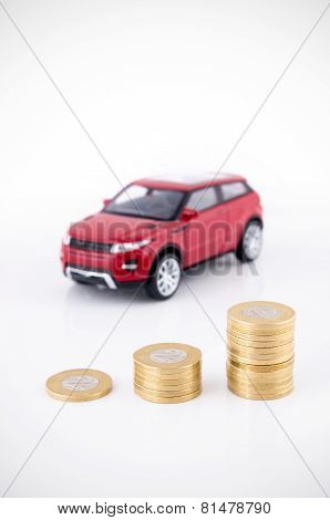 Saving Money To Buy A Vehicle. Coins And Car Toy On White