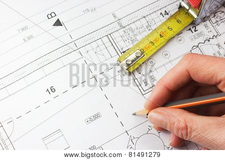 Plan Of A House, Ruler And A Hand Writing With A Pencil