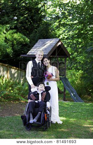 Interracial Bride And Groom Standing With Her Disabled Little Boy In Wheelchair For Wedding Pictures