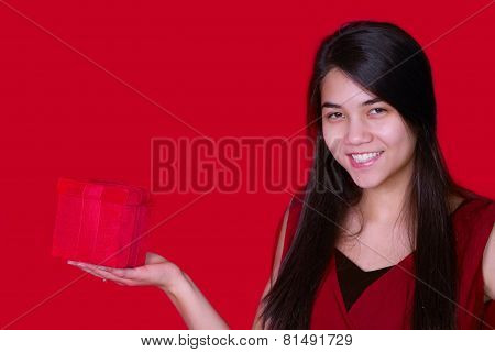 Beautiful Biracial Teen Girl In Red Dress Holding Red Present On Red Background