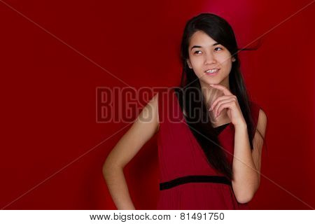 Beautiful Biracial Teen Girl Hand On Chin Thinking. Red Background