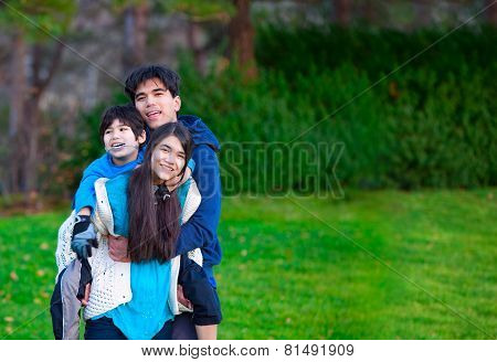 Disabled Biracial Child Riding Piggy Back On His Sister, Family Surrounding Him, Together At Park.
