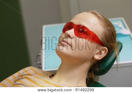 Woman in red safety glasses in dental office