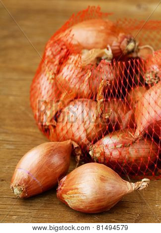 natural organic red shallot onion on a wooden background