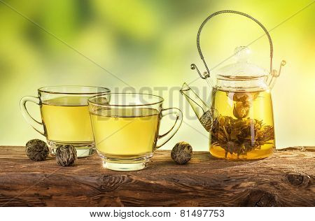 Flowering tea in a teapot on a wooden table