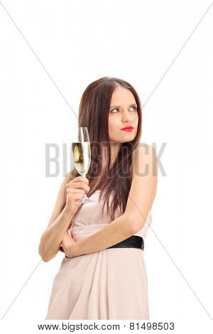 Displeased girl looking at something and holding a glass of wine isolated on white background
