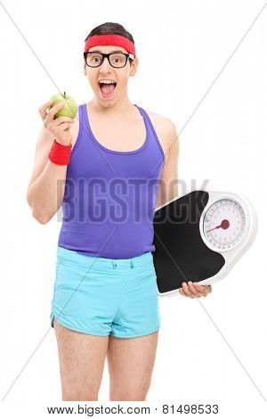 Nerdy guy eating apple and holding a weight scale isolated on white background