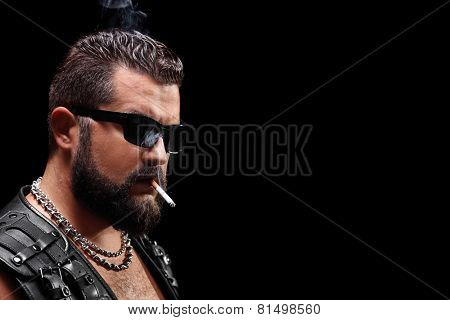 Studio shot of a biker smoking a cigarette on black background