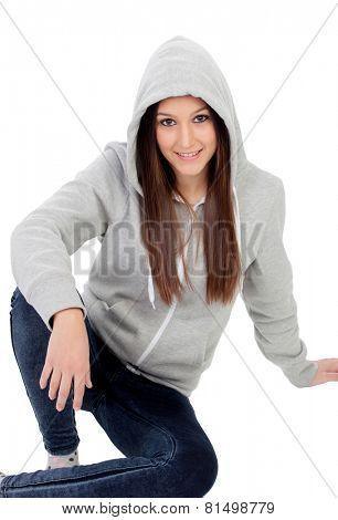 Happy hooded girl with grey sweatshirt sitting on the floor isolated