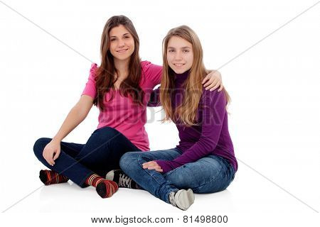 Two different sisters sitting on the floor isolated on a white background