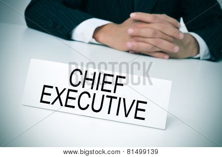 a man in suit sitting at a desk with a signboard in front of him with the text chief executive written in it